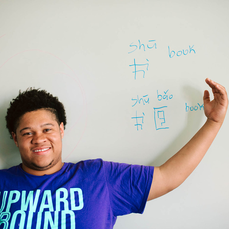 Upward Bound participant writing in a different language on the board.