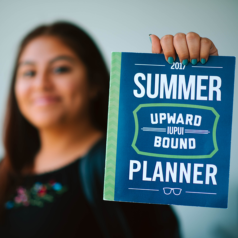 A student holding the summer planner.